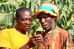 Isaac with a cassava farmer